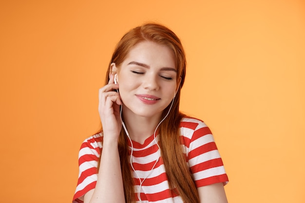 Schöne attraktive rothaarige kaukasische s frau hören musik schließen augen zärtliches lächeln berühren kopfhörer ohr ...