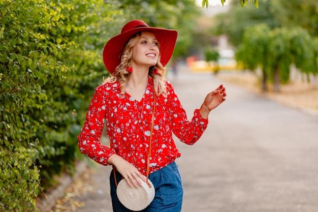 Schöne attraktive stilvolle blonde lächelnde frau in strohrotem hut und bluse sommermode-outfit