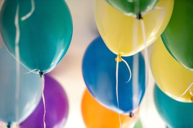 Schöne aufblasbare mehrfarbenballone am raum auf weißem hintergrund