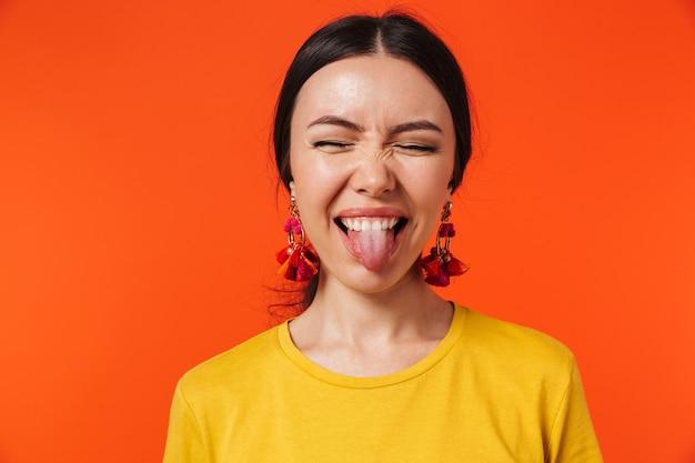 Schöne aufgeregte glückliche junge frau posiert isoliert über orange wand.
