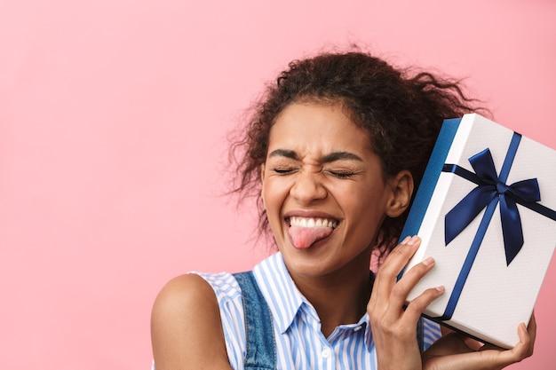 Schöne aufgeregte junge afrikanische frau, die geschenkbox über rosa hält