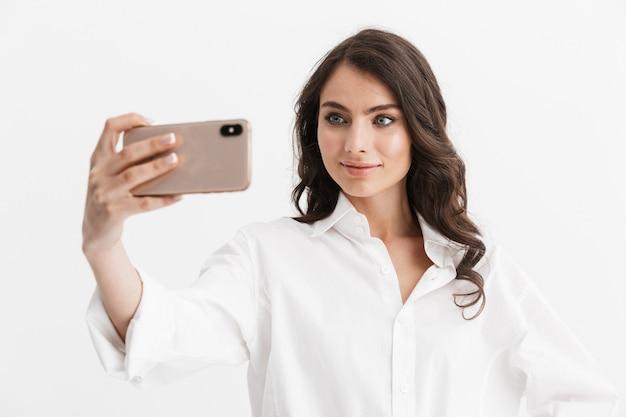 Schöne aufgeregte junge frau mit langen lockigen brünetten haaren, die ein weißes hemd trägt, das isoliert über der weißen wand steht und ein selfie macht