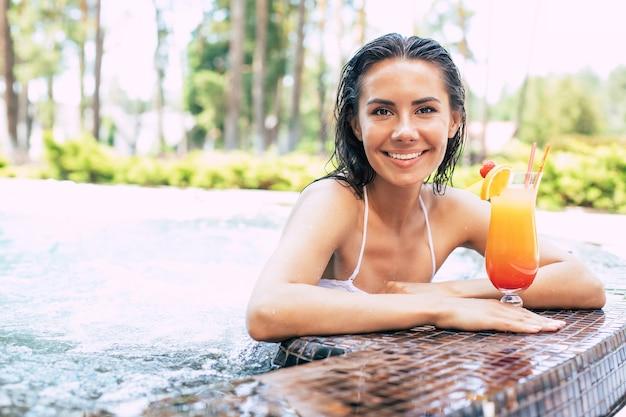 Schöne aufgeregte lächelnde frau entspannt sich im sommerschwimmbad und trinkt erfrischenden cocktail.