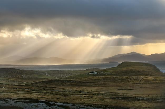 Schöne aufnahme der felder und berge mit sonnenstrahlen, die durch wolken scheinen