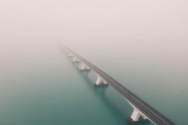 Schöne aufnahme der zeeland-brücke mit nebel in den niederlanden bedeckt