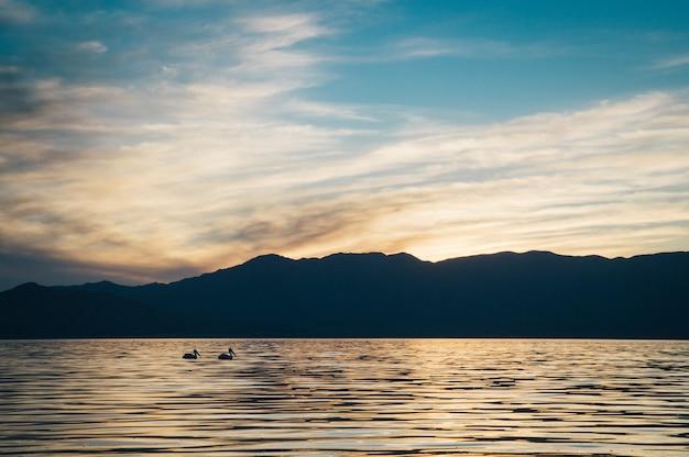 Schöne aufnahme des meeres mit dunklen hügeln und erstaunlichem himmel bei sonnenuntergang