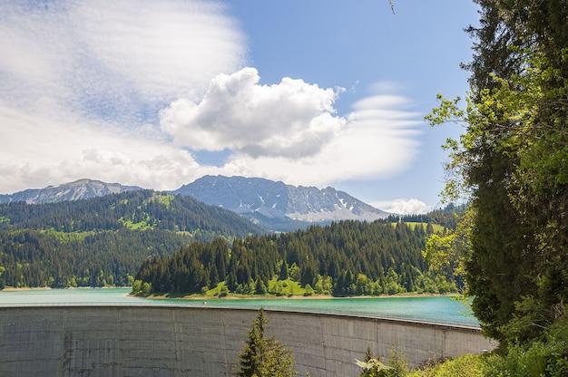 Schöne aufnahme des staudamms lac de l'hongrin mit bergen unter klarem himmel - perfekt für reiseblogs