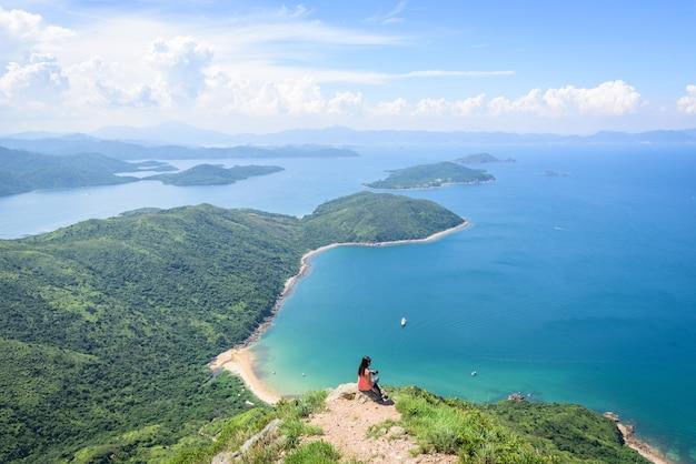 Schöne aufnahme einer frau, die auf einer klippe mit einer landschaft aus bewaldeten hügeln und einem blauen ozean sitzt