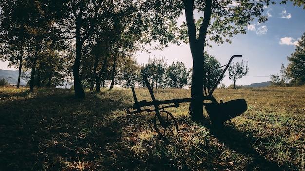 Schöne aufnahme einer silhouette einer konstruktion auf rädern, die neben einem baum in einem ländlichen feld geparkt wird