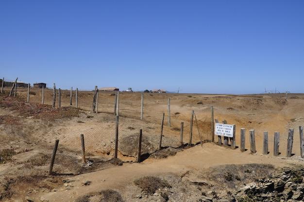 Schöne aufnahme einer wüste in chile durch einen zaun mit gebäuden im hintergrund getrennt