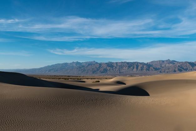 Schöne aufnahme einer wüste mit spuren auf dem sand und felsigen hügeln unter dem ruhigen himmel