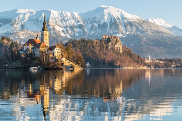 Schöne aufnahme eines hauses in der nähe des sees mit berg ojstrica in bled, slowenien