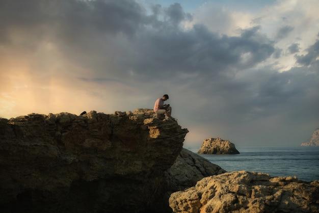 Schöne aufnahme eines mannes, der an der küste sitzt
