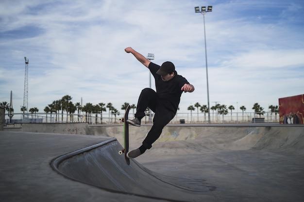 Schöne aufnahme eines mannes skateboarding in einem skatepark während des tages