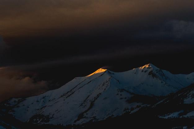 Schöne aufnahme eines mit schnee bedeckten berges während der späten nacht