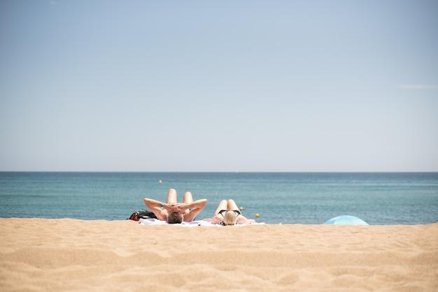 Schöne aufnahme eines paares, das sich am strand unter sonnenlicht entspannt und sonnenbadet