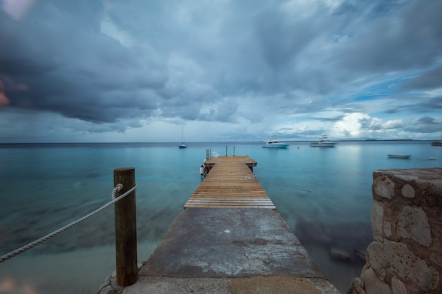 Schöne aufnahme eines piers, der zum ozean unter dem düsteren himmel in bonaire, karibik führt