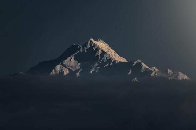 Schöne aufnahme eines schneebedeckten berges bei sonnenuntergang