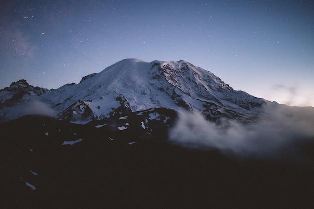 Schöne aufnahme eines schneebedeckten berges, umgeben von natürlichem nebel mit erstaunlichem sternenhimmel