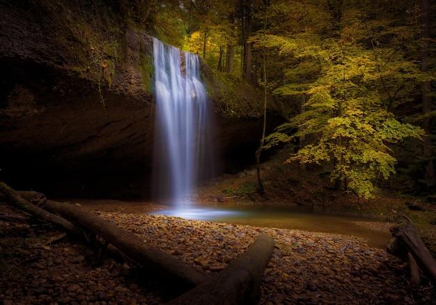 Schöne aufnahme eines wasserfalls, umgeben von herbstbäumen und blättern in einem wald
