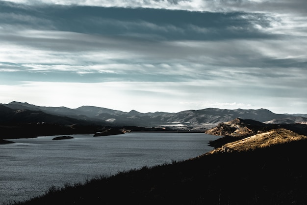 Schöne aufnahme von bergen auf einem seeufer während des sonnenaufgangs