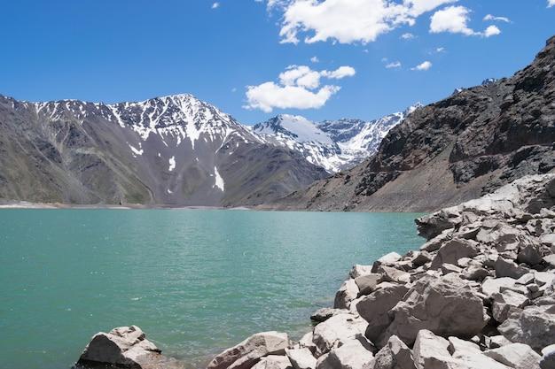 Schöne aufnahme von felsigen bergen und hügeln neben einem see