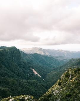 Schöne aufnahme von felsigen grünen bergen und hügeln und erstaunlichem bewölktem himmel während des sonnenuntergangs