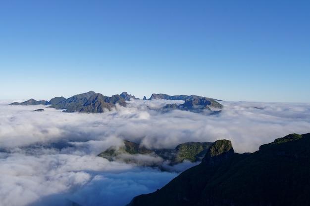 Schöne aufnahme von grünen bergen und hügeln bedeckt in weißen wolken in einem klaren himmel