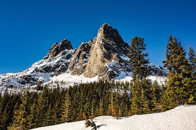 Schöne aufnahme von hohen felsigen bergen und hügeln, die im frühling mit schneeresten bedeckt sind