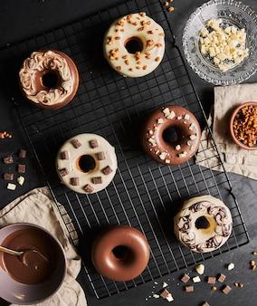 Schöne aufnahme von köstlichen donuts in der glasur mit den zutaten auf einem tisch bedeckt