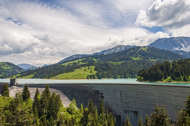 Schöne aufnahme von lac de l'hongrin damm mit bergen unter einem klaren himmel