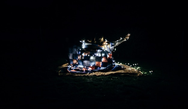Schöne aufnahme von menschen in eine decke gewickelt und weiße lichterketten in der dunkelheit