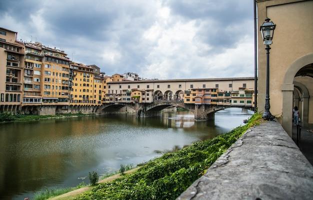 Schöne aufnahme von ponte vecchio in florenz, italien mit einem bewölkten grauen himmel im hintergrund