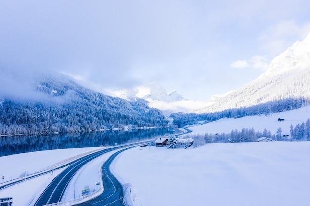Schöne aufnahme von schneebedeckten bergen, holzhäusern und einem see, der die bäume reflektiert