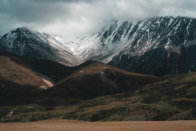 Schöne aufnahme von schneebedeckten felsigen bergen und hügeln unter einem nebligen bewölkten himmel