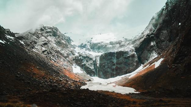 Schöne aufnahme von schneebedeckten und felsigen bergen, die an einem sonnigen tag mit nebel bedeckt sind