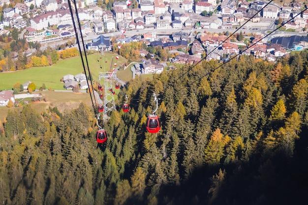 Schöne aufnahme von seilbahnen über einem bewaldeten berg mit gebäuden in der ferne