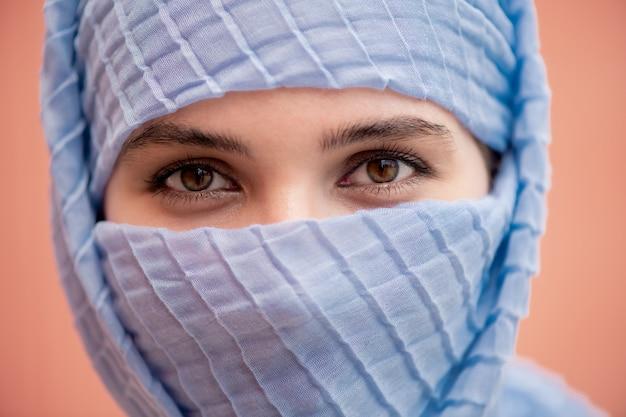 Schöne augen der jungen muslimischen frau mit ihrem gesicht versteckt hinter blauem hijab, der sie ansieht