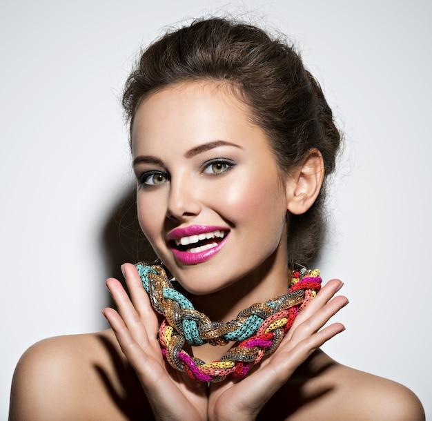 Schöne ausdrucksstarke frau mit hellem schmuck und schönheitsmodefoto