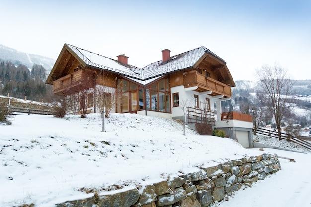 Schöne aussicht auf das holzhaus in den österreichischen alpen mit show bedeckt