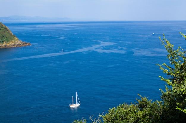 Schöne aussicht auf das meer und die schwimmende yacht am sonnigen tag
