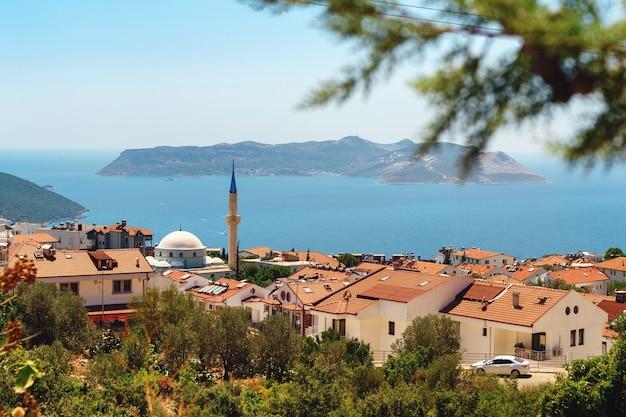 Schöne aussicht auf das türkisfarbene meer mit einer moschee und türkischen häusern im vordergrund, dem ferienort kas, türkei. seestück in der türkei