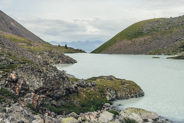 Schöne aussicht auf den bergsee im hintergrund der berge am horizont unter bewölktem himmel. atmosphärische grüne landschaft mit see im hochtal. tolle landschaft mit bergsee im highland glen