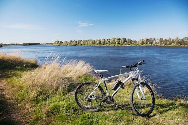 Schöne aussicht auf den fluss, ein mountainbike ist auf einem hintergrund des flusses an einem klaren sonnigen tag, fahrrad in der natur, blaues wasser und himmel