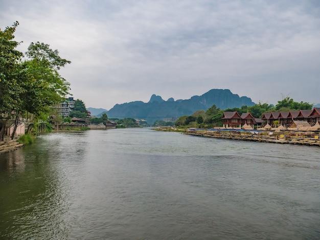 Schöne aussicht auf den fluss nam song mit restaurant am flussufer und den bergen in der stadt lao in vangvieng.