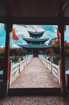 Schöne aussicht auf den jade dragon snow mountain und die suocui bridge über den black dragon pool im jade spring park, lijiang, yunnan
