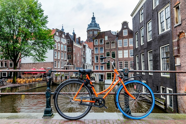Schöne aussicht auf den kanal in amsterdam. häuser auf dem wasser, fahrräder mit blumen nm brücke. tolles stadtbild.