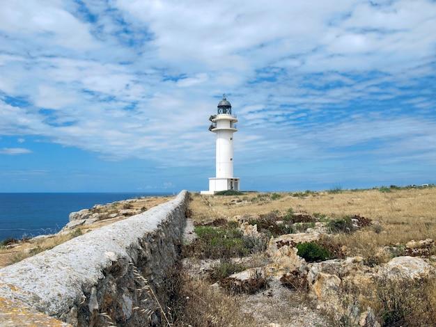 Schöne aussicht auf den leuchtturm auf einer klippe bei bewölktem himmel in formentera, spanien
