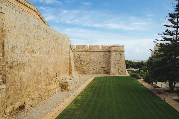Schöne aussicht auf den park in der nähe des alten gebäudes von mdina gate in malta unter dem blauen himmel