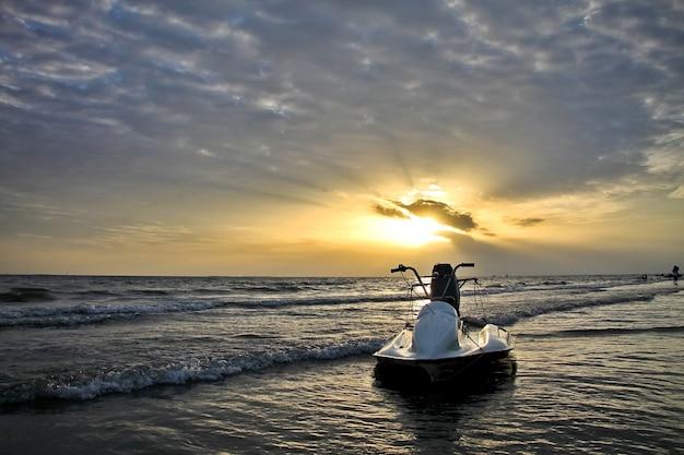 Schöne aussicht auf den sonnenuntergang mit lichtstrahl, wolke und weißen jetski am strand. low key. natur- und sportkonzept.